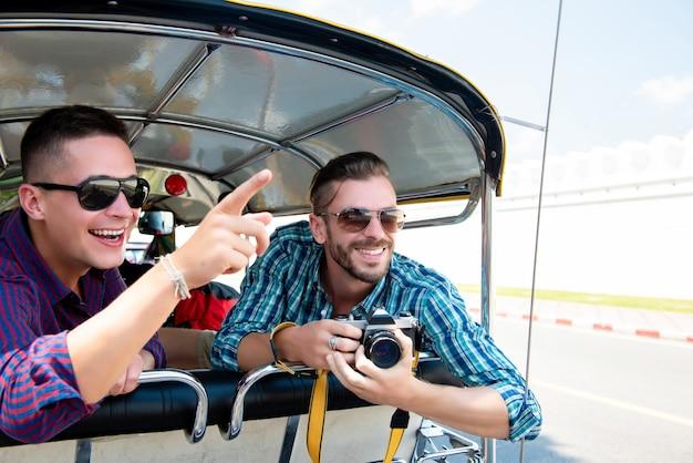 Toeristen die en pret op tuk tuk-taxi in thailand hebben opgewekt zijn