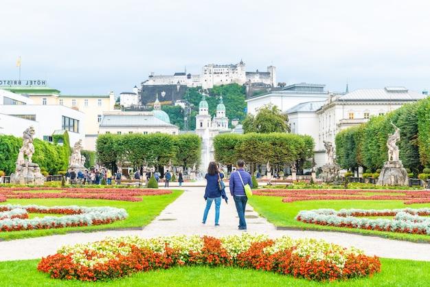 Toeristen die rond mirabell-paleis en tuinen lopen