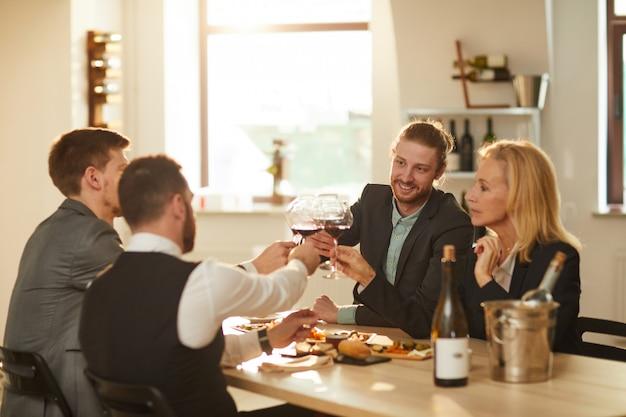 Toeristen die wijn drinken bij wijngaard