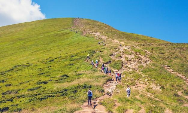 Toeristen gaan de berg op via een steil rotsachtig pad. verovering van de berg