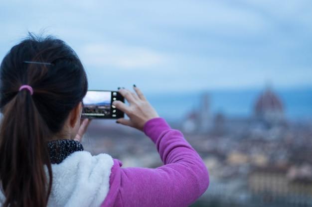 Toeristen gebruiken mobiele foto's om foto's te maken op het uitkijkpunt in florance, italië.