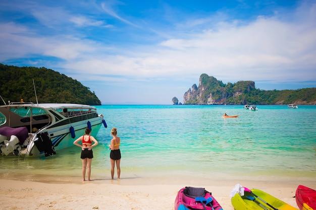 Toeristen genieten van uitzicht op het eiland phi phi op het zandstrand zonnige dag op het tropische eiland kajaks op zand