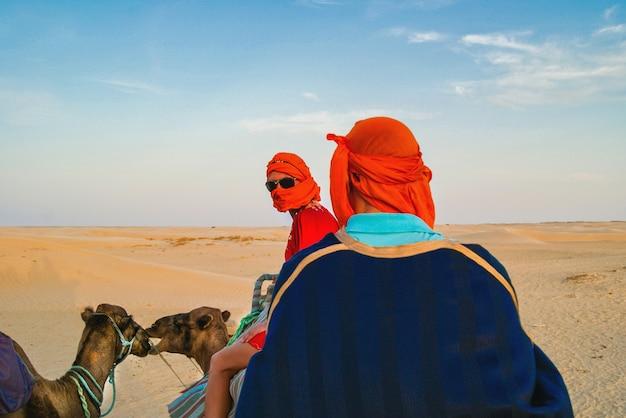 Toeristen in de sahara woestijn op kamelen. het vermaak van toeristen.