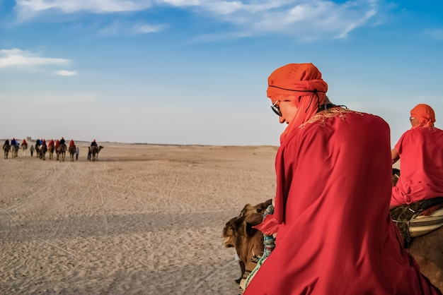 Toeristen in de woestijn op kamelen. het vermaak van toeristen.