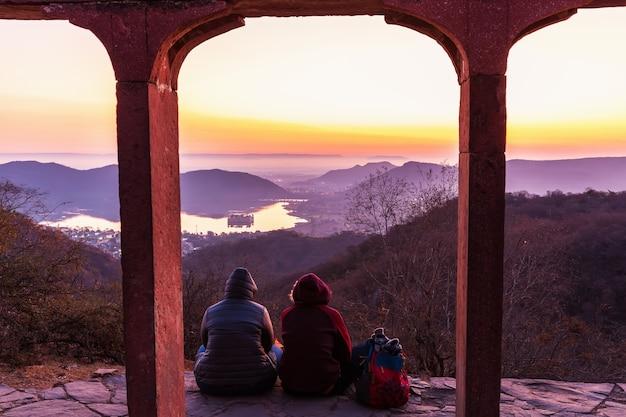 Toeristen kijken naar de zonsopgang boven jal mahal palace, india, jaipur.