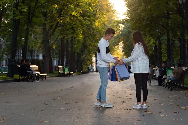 Toeristen lopen in het herfstpark met papieren boodschappentassen.