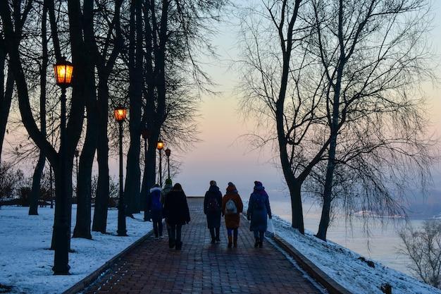 Toeristen lopen langs de oever van de rivier de wolga