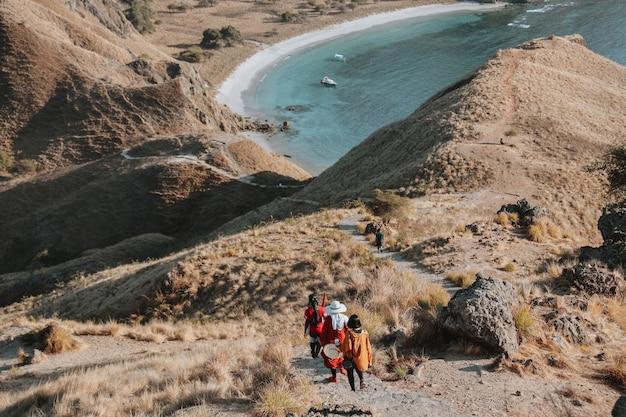 Toeristen lopen over de savanneheuvel op padar island