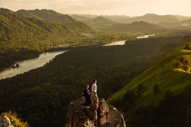 Toeristen man en vrouw met rugzakken op de top van de berg kijken naar de vallei