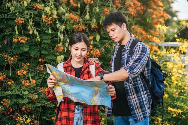 Toeristen, mannen en vrouwen, kijken naar de kaart bij de bloementuinen.