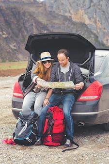 Toeristen met een kaart en rugzakken in de auto in de bergen