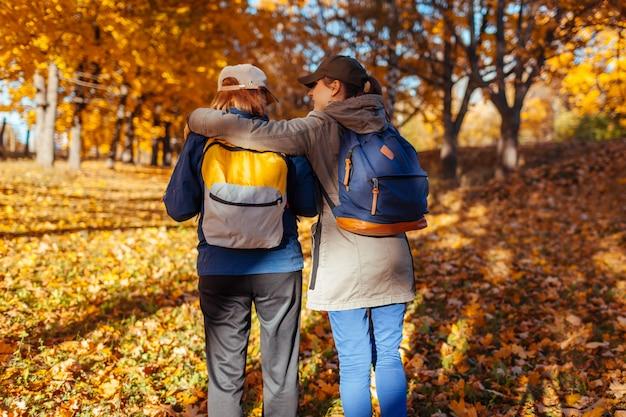 Toeristen met rugzakken wandelen in herfst bos moeder en haar volwassen dochter die samen reizen
