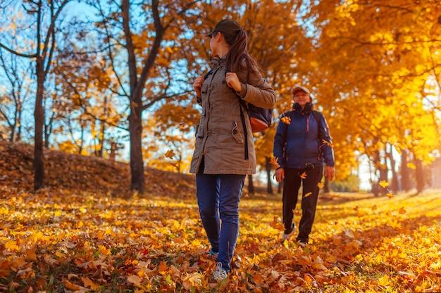 Toeristen met rugzakken wandelen in herfst bos moeder en haar volwassen dochter reizen
