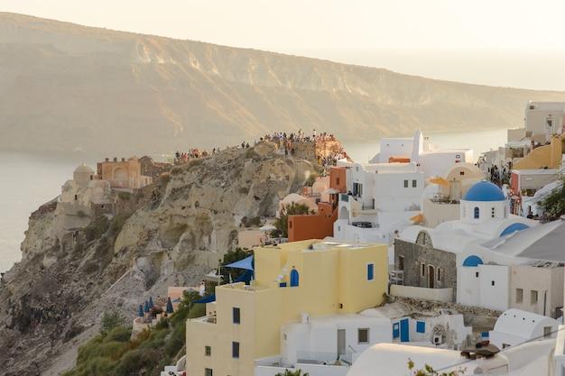 Toeristen ontmoeten de zonsondergang in het dorp oia, santorini.