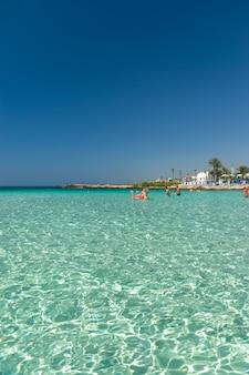Toeristen ontspannen en zwemmen op een van de populairste stranden van het eiland.