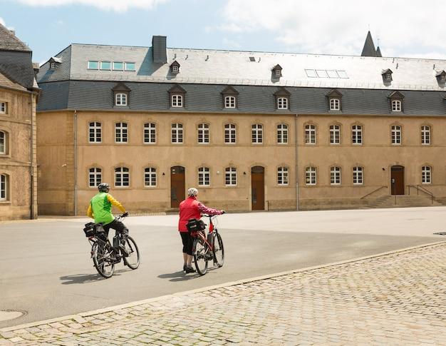 Toeristen op fietsen, oude europese stadsstraat