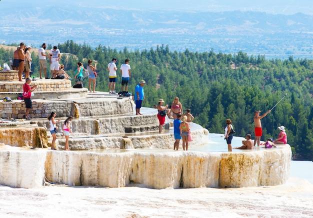 Toeristen op pamukkale travertijn zwembaden en terrassen.