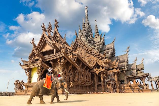 Toeristen rijden olifanten rond het heiligdom van de waarheid in pattaya, thailand