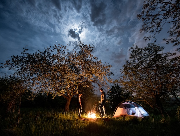 Toeristen staan bij een kampvuur in de buurt van tent