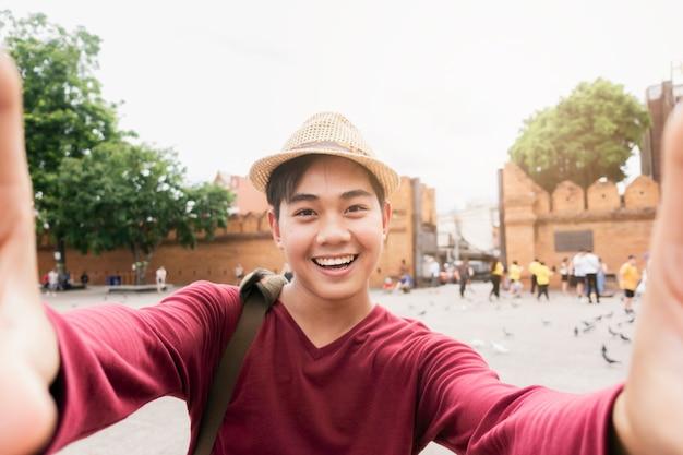 Toeristen voelen zich gelukkig en plezierig en gebruiken een camera om een selfie te maken.