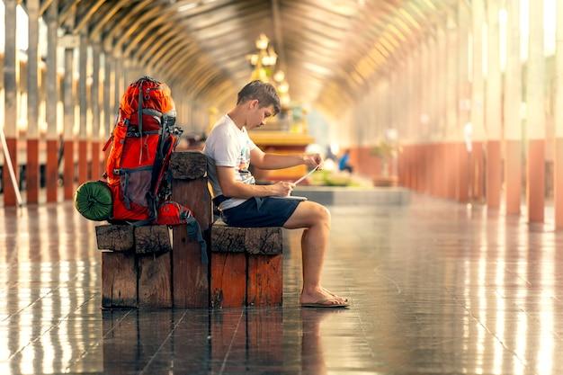 Toeristen werken vanuit de laptop op het treinstation terwijl ze wachten op de trein.