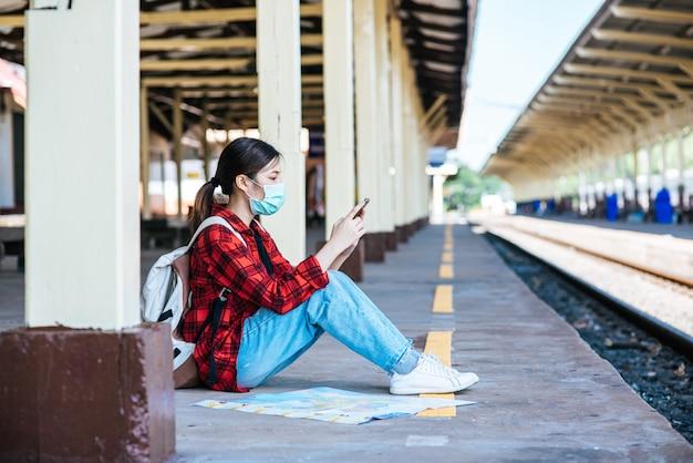 Toeristen zitten en kijken naar telefoons op het voetpad naast de spoorlijn.