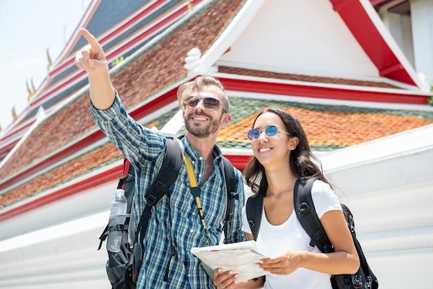Toeristenbackpackers die in oude thaise tempel op vakanties in thailand reizen