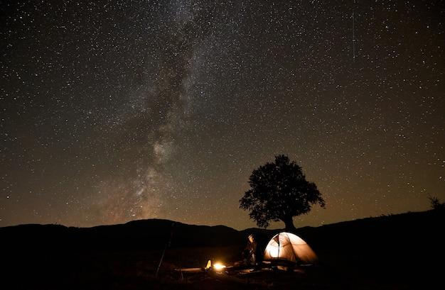 Toeristenfotograaf bij kampvuur voor tent, fotocamera op statief onder donkere sterrenhemel.