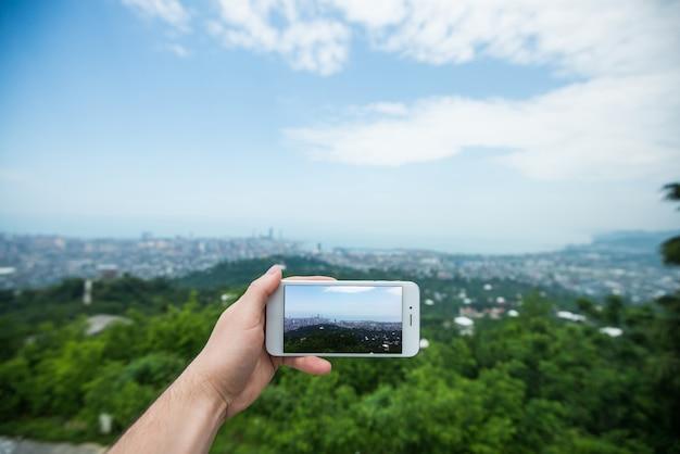 Toeristenhand die slimme telefoon houden, die foto van batumi-stad, georgië nemen