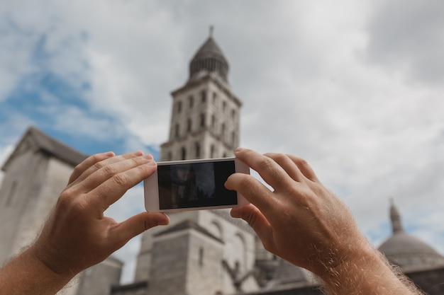 Toeristenhanden die slimme telefoon houden die foto van perigueux, frankrijk nemen