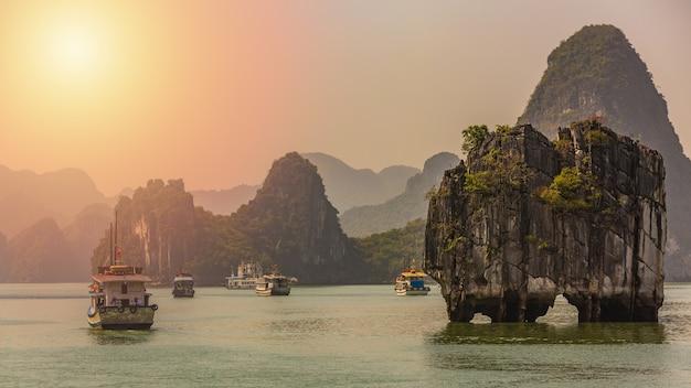 Toeristenjonken die onder kalksteenrotsen bij ha long-baai drijven