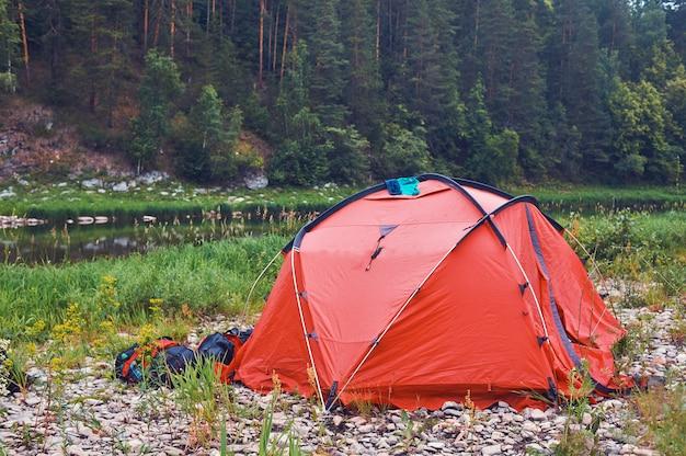 Toeristenkamp aan de rivier. tenten onder de blauwe lucht. raften op een bergrivier.