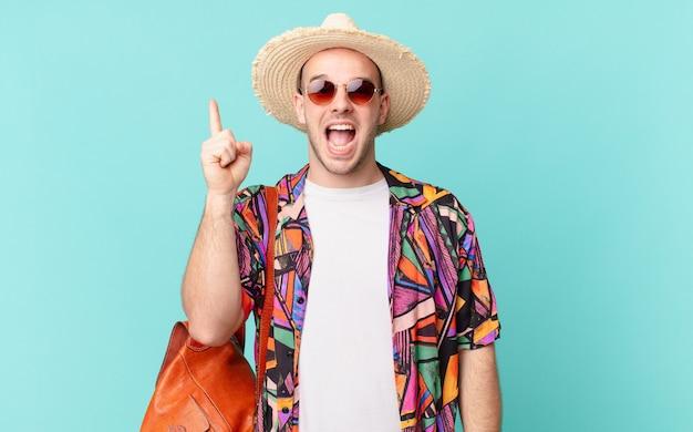 Toeristenman die zich als een blij en opgewonden genie voelt na het realiseren van een idee, vrolijk de vinger op te steken, eureka!