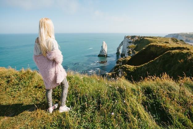 Toeristenmeisje dat van hierboven naar de baai en de albasten klifbaai van etretat, frankrijk kijkt