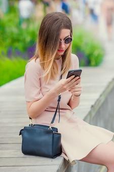 Toeristenmeisje die messgae verzenden door smartphone op de zomervakantie. jonge aantrekkelijke vrouw met mobiele telefoon die in openlucht van de bestemming van de vakantiereis in toerisme geniet en concept onderzoekt