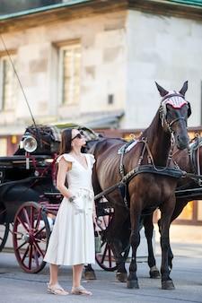 Toeristenmeisje die van een wandeling door wenen genieten en de mooie paarden in het vervoer bekijken