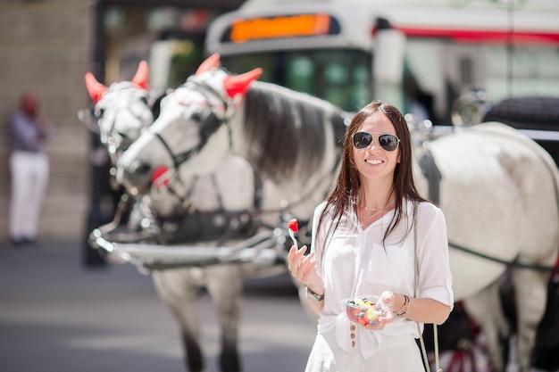 Toeristenmeisje die van vakantie in wenen genieten en de mooie paarden in het vervoer bekijken