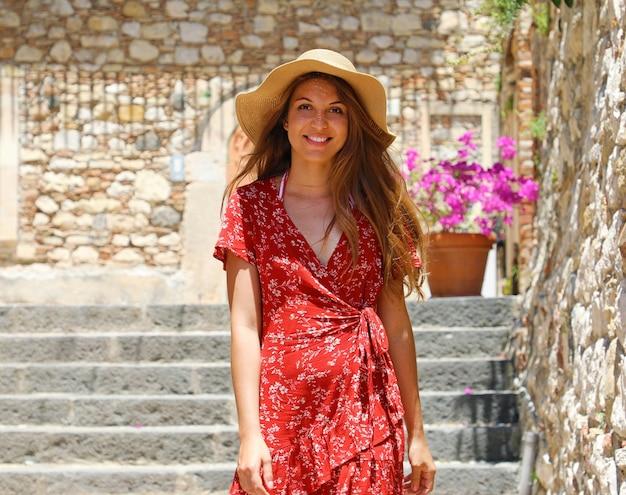 Toeristenmeisje met hoed en rode kleding die in gezellige italiaanse straat in taormina, sicilië lopen