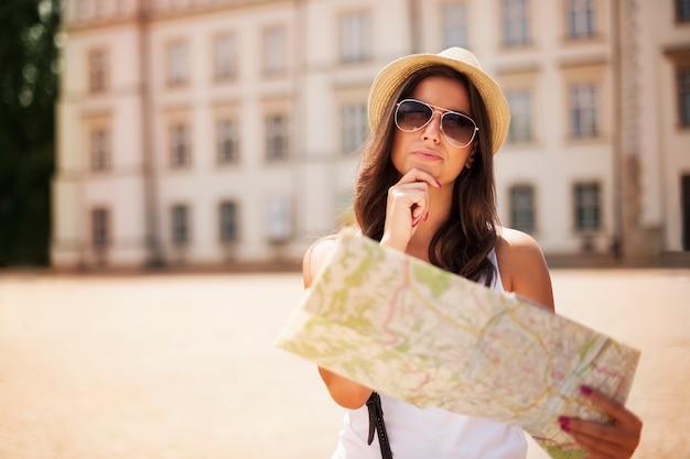 Toeristenmeisje met kaart die zich afvraagt waar ze heen moet