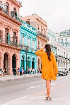 Toeristenmeisje op populair gebied in havana, cuba. achteraanzicht van jonge vrouw reiziger glimlachen