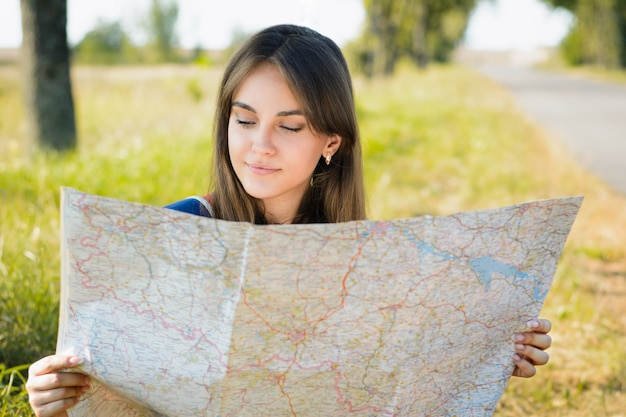 Toeristenmeisje reizende liftzitting dichtbij de weg die een pauze hebben of een rust hebben terwijl het reizen in het platteland