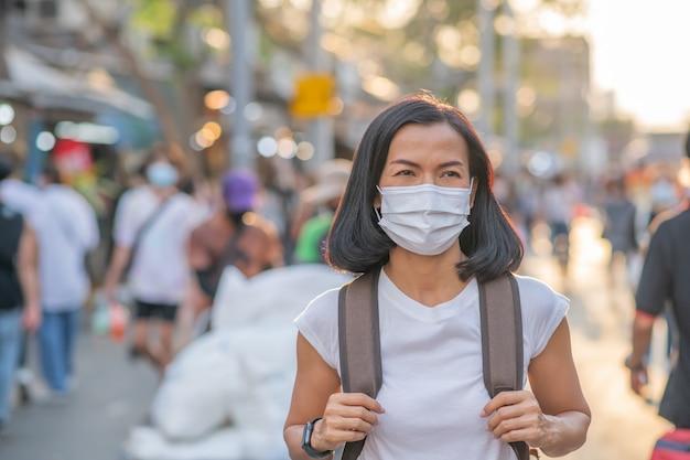 Toeristenmeisjes die gezichtsmaskers dragen ar straat.
