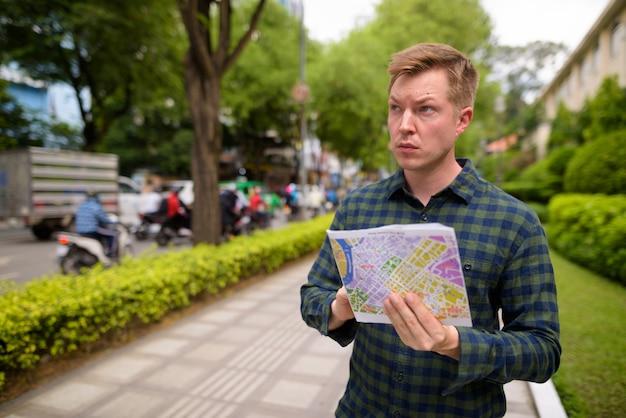 Toeristenmens die ho chi minh-stad in vietnam onderzoeken en kaart houden