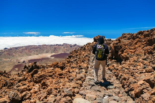 Toeristenmens met rugzak die rond de bovenkant van de vulkaan teide in tenerife, canarische eilanden, spanje lopen