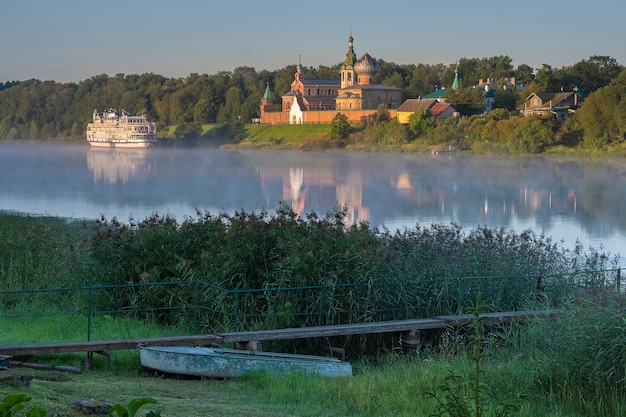 Toeristenmotorschip tegen de achtergrond van het mannelijke nikolsky-klooster in staraya ladoga