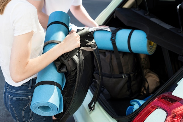 Toeristenpaar die klaar voor reis met rugzakken in auto worden