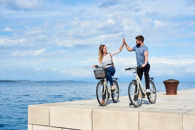 Toeristenpaar die zich met fietsen op verharde steenstoep door het overzees bevinden