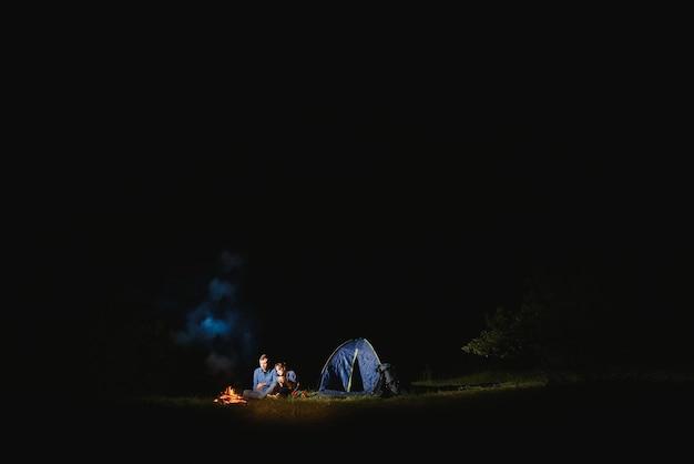 Toeristenpaar zit verlichte tent verlicht door brandend kampvuur