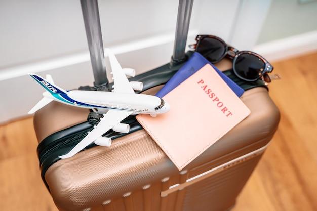 Toeristenpaspoorten, een speelgoedvliegtuig op een reiskoffer. conceptuele foto van een toeristische reis