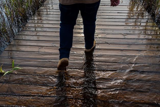 Toeristenpersoon die op de overstroomde voetgangersbrug van meer albufera loopt.